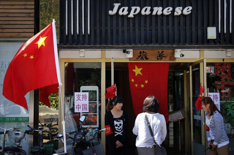 Workers from a Japanese restaurant, located near the Japanese embassy, smile at a customer as she walks through their entrance past Chinese national in Beijing