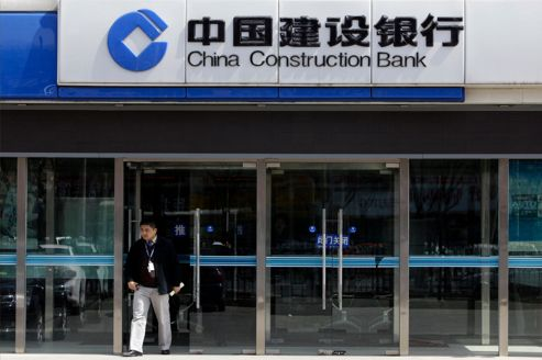 Man walks out of China Construction Bank branch in Beijing g